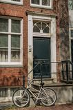 Cykla framme av trappa till ingången av stilfull gammal tegelstenbyggnad i Amsterdam Royaltyfri Foto