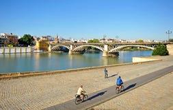 Cykla i Seville på den Guadalquivir floden och panoramautsikten av den Triana bron, Spanien royaltyfri bild