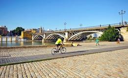 Cykla i Seville på den Guadalquivir floden och panoramautsikten av den Triana bron, Spanien arkivfoto