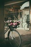 Cykla med blommor i korgen som ligger bredvid väggen Royaltyfria Foton