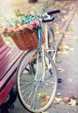 Cykla med blommor som korgen parkerar in nära bänk signalbild Arkivbilder