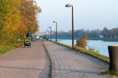 Cykla med cirkuleringssläpet för barn bredvid en flod Royaltyfri Foto