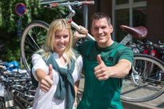 Cykla mekanikern och kunden i cykellagret som ger upp tummar Arkivfoton