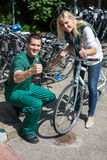 Cykla mekanikern och kunden i cykellagret som ger upp tummar Royaltyfri Bild