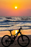 Cykla på strandskymningtiden royaltyfri foto