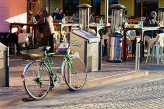Cykla parkerat och folk som dricker i gatakafé i Ljubljana royaltyfria bilder