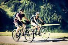 Cykla pensionärer vid sjön Arkivbild
