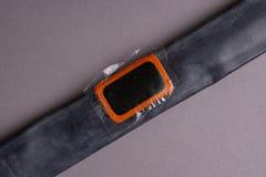 Cykla reparationssatsen, hjulkamera på träbakgrund Lapp på kameran av cykeln arkivfoto
