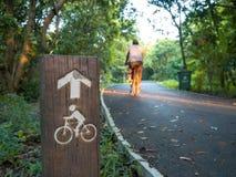 Cykla riktningstecknet bredvid vägen parkerar in med oskarpt rida M Arkivfoton