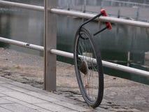 Cykla stulit och att lämna endast ett hjul som låsas fortfarande för att belägga med metall räcket royaltyfri foto