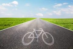 Cykla symbolet på den långa raka asfaltvägen, väg Royaltyfri Foto