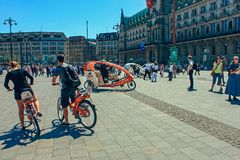 Cykla taxien för turister på marknadsfyrkanten med det Hamburg stadshuset Rathaus och blå himmel nära sjön Alster Binnenalster in royaltyfria bilder