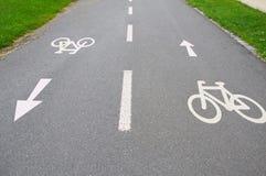 Cykla tecken med pilar på vägvisningen mitt emot riktningar Arkivfoto