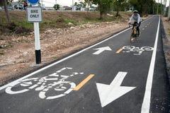 Cykla tecknet eller symbolen och rörelse av cyklisten i cykelgränden Fotografering för Bildbyråer