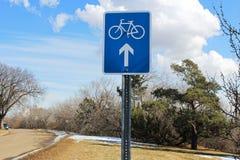 Cykla tecknet för rutten framåt längs en scenisk gata royaltyfri foto