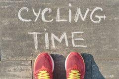 Cykla tid, text på den gråa trottoaren med kvinnaben i gymnastikskor, bästa sikt royaltyfri bild