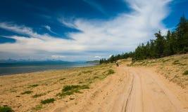 Cykla turist- gå vid den sandiga vägen i dyn längs laken Fotografering för Bildbyråer