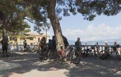 Cykla turister som stoppas för att vila i skuggig fläck på promenaden av semesterorten Gelendzhik Royaltyfri Foto
