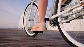 Cyklar den övre sikten för slutet av den unga stilfulla flickan i rosa plattformskobrogues och kjolen som cyklar på tappning, på  stock video