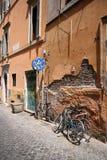 cyklar den typiska under väggen för den italienska gatan Royaltyfri Foto