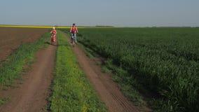 cyklar familjen En kvinna med ett barn på en ritt på cyklar livsstil Sund livsstil sportfamilj arkivfilmer