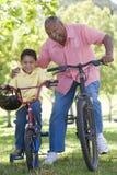 cyklar farfarsonsonen som ler utomhus Fotografering för Bildbyråer