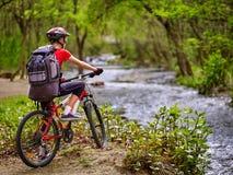 Cyklar flickan med den stora ryggsäcken som cyklar att vada över genom hela vatten Royaltyfria Bilder