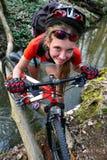 Cyklar flickan som cyklar att vada över genom hela vatten Royaltyfri Bild