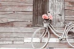 Cyklar gamla tappningblommor i en korg parkerat fotografering för bildbyråer