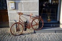 Cyklar gammal tappning danade rosa färger stöttat av ett antikt shoppar väggen royaltyfria bilder