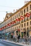 Cyklar i Rue Corraterie Street med schweiziska flaggor i Genève arkivbild