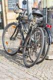 Cyklar lutar mot en lykta bredvid en soptunna Arkivbilder