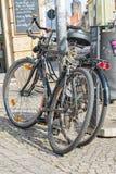 Cyklar lutar mot en lykta bredvid en soptunna Royaltyfria Foton