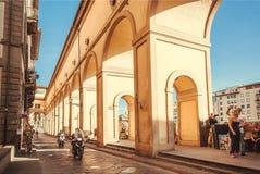 Cyklar och folk på gatan med historiska bågar av den forntida Tuscany staden royaltyfria foton