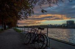 Cyklar och solnedgång på sjöarna, i Köpenhamn Arkivfoton