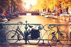 Cyklar på bron i Amsterdam, Nederländerna Fotografering för Bildbyråer