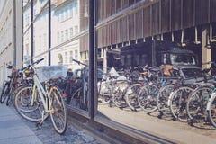 Cyklar på en gata bredvid shoppafönstret i Köpenhamnen, Denm Arkivfoton