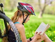 Cyklar som cyklar den bärande hjälmen för flickan, läste boken vilar nära cykeln Fotografering för Bildbyråer