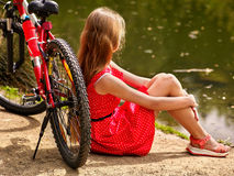 Cyklar som cyklar flickan in i, parkerar Flickan sitter benägenhet på cykeln på kust Royaltyfria Foton