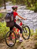 Cyklar som cyklar flickan med den stora ryggsäcken som cyklar att vada över genom hela vatten Royaltyfri Bild