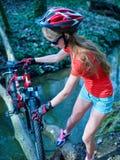 Cyklar som cyklar flickan som cyklar att vada över genom hela vatten Royaltyfria Foton