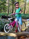 Cyklar som cyklar flickan som cyklar att vada över genom hela vatten Royaltyfri Bild
