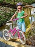 Cyklar som cyklar flickan som cyklar att vada över genom hela vatten Royaltyfri Foto