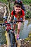 Cyklar som cyklar flickan som cyklar att vada över genom hela vatten Arkivfoton