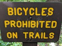 Cyklar som förbjudas på slingor, undertecknar, gula bokstäver på brunt tecken arkivfoto