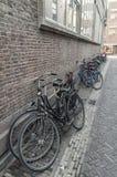 Cyklar som förläggas mot väggen i gatan arkivfoton