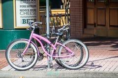 Cyklar som framme låsas till ett gatatecken av en New Orleans stång Arkivfoton