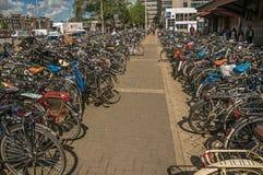 Cyklar som framme parkeras på gatan av den Amsterdam centralstationen fotografering för bildbyråer