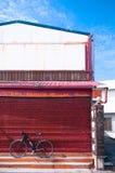Cyklar som parkerar mot den röda lantliga väggen av lagret Royaltyfri Bild