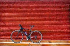 Cyklar som parkerar mot den röda lantliga väggen av lagret Arkivfoton